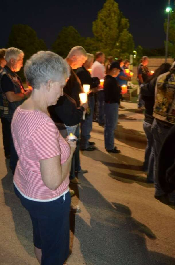Sue Burdette honors her missing husband at the Vietnam Memorial wall at the Midland International Airport Friday night. Burdette's husband, Lonnie Pat Bogard, was one of 1,741 American personnel listed as missing by the Department of Defense. He went missing May 12, 1972 while flying an F-4 Phantom fighter during a night mission over North Vietnam. Although his plane was located about six years ago by his co-pilot's dog tags, Bogard's body has still not been found. Political and weather-related issues have prevented a full excavation of the wreckage and remains. Photo: James Cannon/Reporter-Telegram
