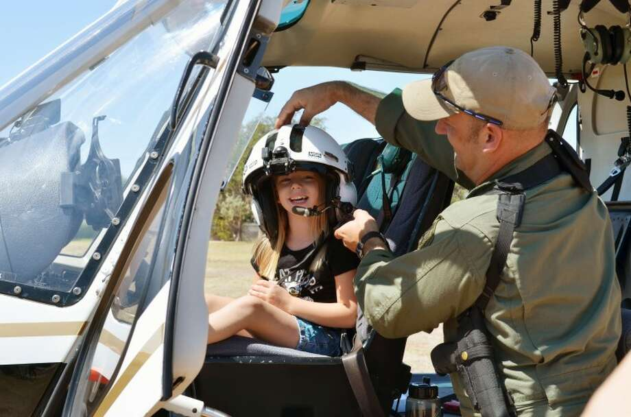 A Midland police officer�s daughter sits in a Department of Public Safety helicopter at Midland College Saturday afternoon during the Women in Criminal Justice event. James Cannon/Reporter-Telegram Photo: James Cannon