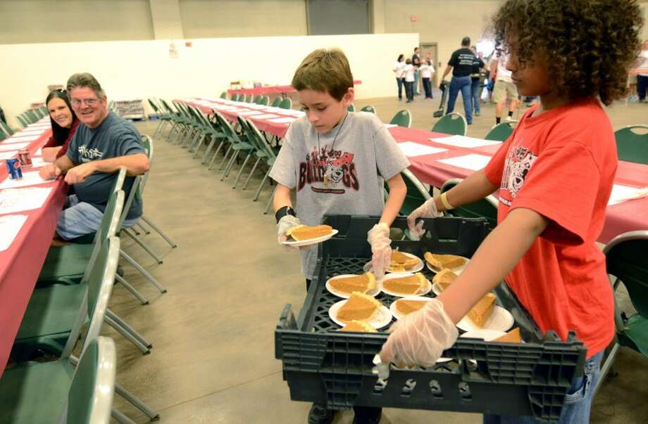 Hayden Pike and Felton Walton, 4th graders at Bowie Fine Arts Academy, serve slices of pumpkin pie during the annual H.E.B. Feast of Sharing, a free community Thanksgiving dinner Friday at Horseshoe Arena. James Durbin/Reporter-Telegram Photo: JAMES DURBIN