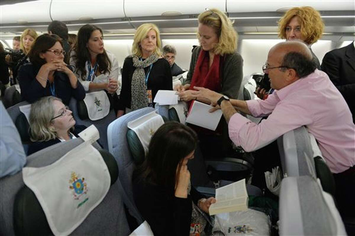 (File Photo) Journalists prepare their questions prior to a Pope Francis' news conference aboard the papal flight on the journey back from Brazil, Monday, July 29, 2013. Pope Francis reached out to gays on Monday, saying he wouldn't judge priests for their sexual orientation in a remarkably open and wide-ranging news conference as he returned from his first foreign trip.