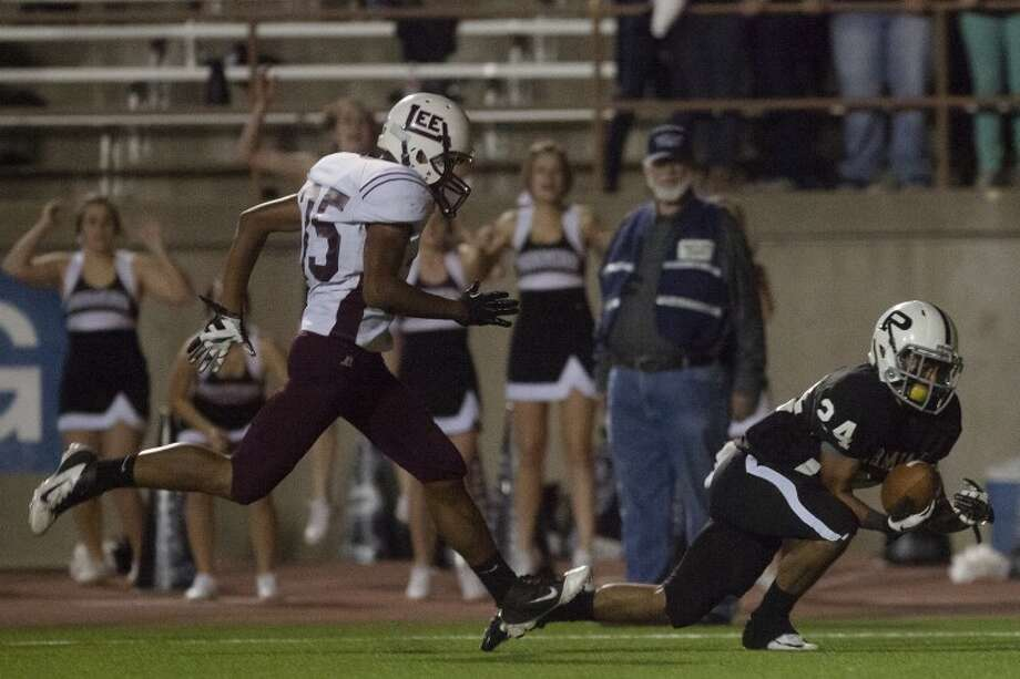 Permian's Andrew Perez (24) catches a touchdown pass as Midland Lee's Alex Bell (35) guards him during the game Friday at Ratliff Stadium. The touchdown put Permian behind by two points, 12-14, but a two point conversion tied the game at 14 all. Photo: Albert Cesare|Odessa American