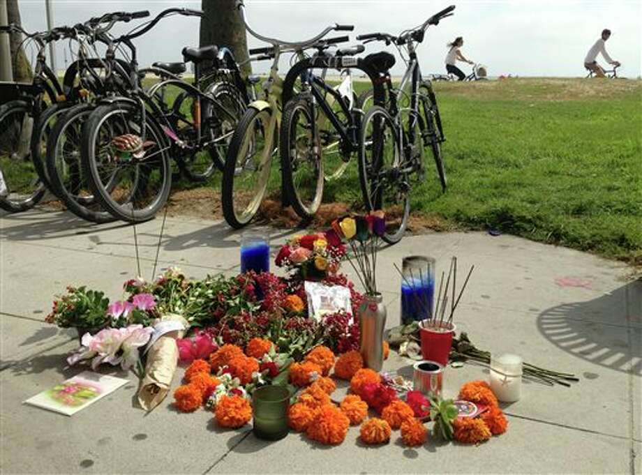 A makeshift memorial along the Venice, Calif., beach boardwalk is shown Sunday Aug. 4, 2013 near where a Saturday incident involving a driver who accelerated through a crowd of beachgoers, hitting one person after another as bystanders tried desperately to get out of the way. The hit-and-run killed an Italian woman on her honeymoon and hurt 11 others. (AP Photo/Tami Abdollah) Photo: Tami Abdollah / AP