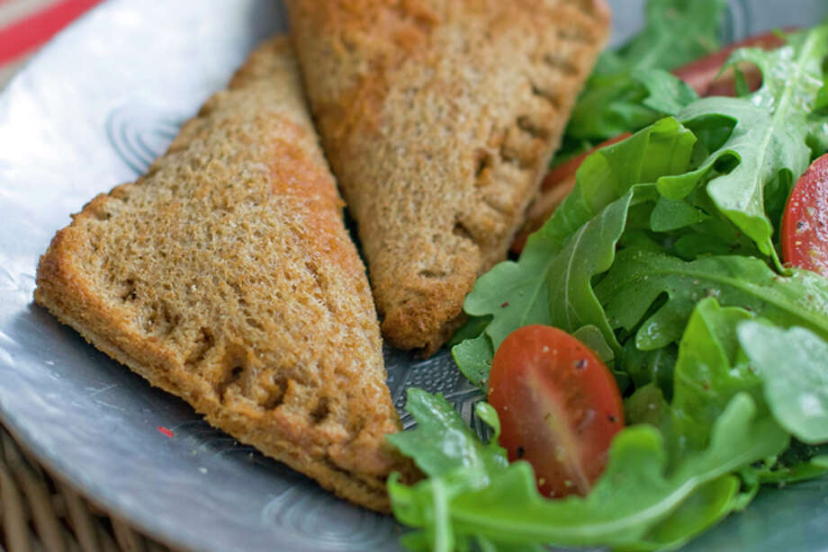 This Sept. 8, 2011 photo shows pizza pockets in Concord, N.H. Rocco DiSpirito's pizza pockets are made using whole-wheat bread and stuffed with traditional pizza toppings. (AP Photo/Matthew Mead) Photo: Matthew Mead / FR170582 AP