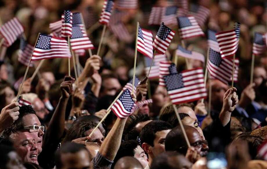 Supporters wave flags during President Barack Obama's election night party Tuesday, Nov. 6, 2012, in Chicago. President Obama defeated Republican challenger former Massachusetts Gov. Mitt Romney. (AP Photo/M. Spencer Green) Photo: M. Spencer Green / AP