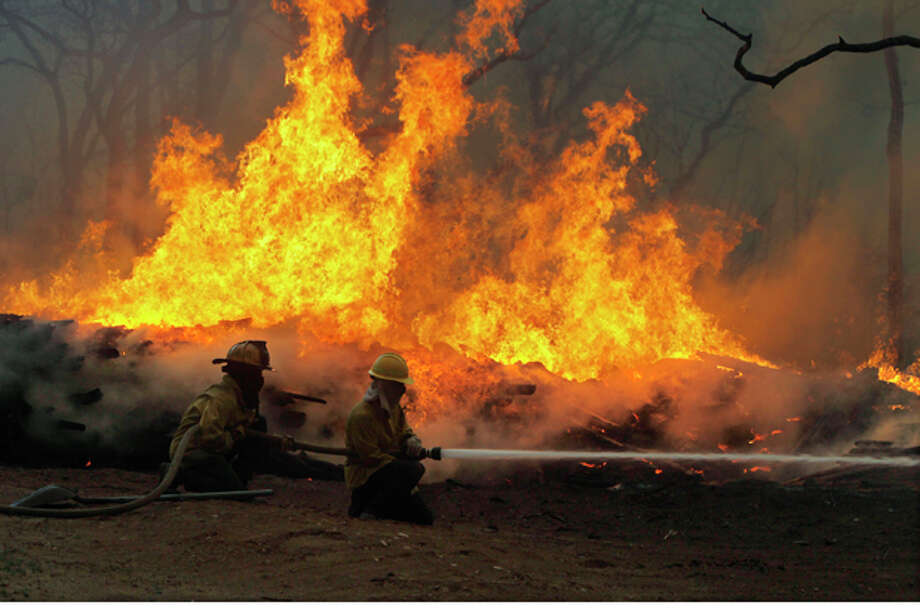 File - In this Sept. 5, 2011 file photo firefighters battle a wildfire on Highway 71 near Smithville, Texas. Scorching temperatures, strong winds and dry vegetation are turning Texas wildfires into fast and furious dangers that hop from place to place within hours, even minutes, and give residents little time to flee. Now it's likely to get worse. (AP Photo/Erich Schlegel, File) Photo: Erich Schlegel / FR 62355 AP