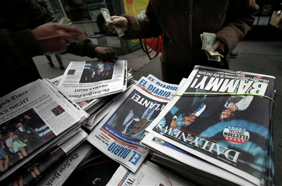 A news dealer sells copies of his papers on New York's Upper West Side, Wednesday, Nov. 7, 2012. President Barack Obama won Ohio, Wisconsin, Virginia, Iowa, New Hampshire, Colorado and Nevada, seven of the nine battleground states. Romney captured only North Carolina. The final swing state ó Florida ó remained too close to call. (AP Photo/Richard Drew) Photo: Richard Drew / AP