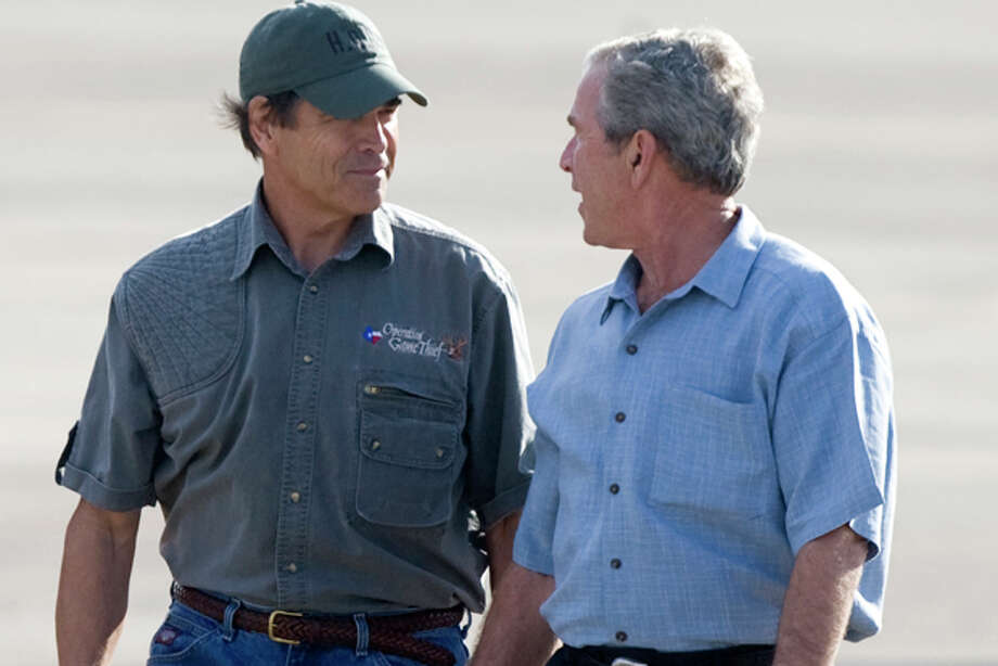 FILE - In this photo Sept. 16, 2008, file photo then-President George W. Bush, right, talks with Texas Gov. Rick Perry, as he arrives in Houston to tour damage in Galveston from Hurricane Ike. With Perry running for president in 2012, the spotlight is shining on the tense relationship between the two Texans and their allied camps. In public, both Perry and Bush shrug off any friction. (AP Photo/Bob Levey, File) Photo: Bob Levey / FR156786 AP