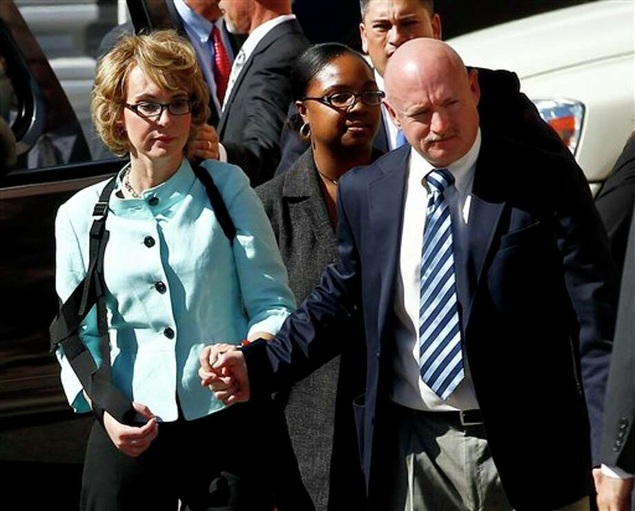 Former Democratic Rep. Gabrielle Giffords, left, and her husband Mark Kelly leave after the sentencing of Jared Loughner, in back of U.S. District Court Thursday, Nov. 8, 2012, in Tucson, Ariz. U.S. District Judge Larry Burns sentenced Jared Lee Loughner, 24, to life in prison, for the January 2011 attack that left six people dead and Giffords and others wounded. Loughner pleaded guilty to federal charges under an agreement that guarantees he will spend the rest of his life in prison without the possibility of parole. (AP Photo/Ross D. Franklin) Photo: Ross D. Franklin / AP