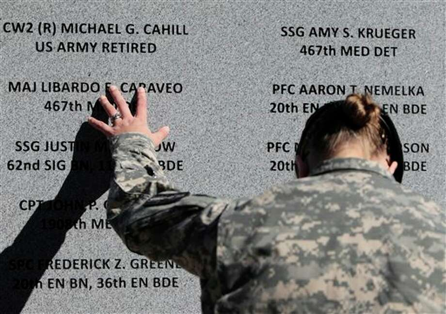 FILE- In this Nov. 5, 2010, file photo, Staff Sgt. Joy Clark of the 467th Combat Stress Control Detachment takes a moment to run her fingers over the engravings of the names of her fellow soldiers at a ceremony commemorating the one-year anniversary of the worst mass shooting on a U.S. military base, in Fort Hood, Texas. Maj. Nidal Hasan is charged in the 2009 shooting rampage at Fort Hood that left 13 dead and more than 30 others wounded. Hasan doesn't deny that he carried out the rampage, but military law prohibits him from entering a guilty plea because authorities are seeking the death penalty. If he is convicted and sentenced to death in a trial that starts Tuesday, Aug. 6, 2013, there are likely years, if not decades, of appeals ahead. (AP Photo/The Dallas Morning News, Sonya N. Hebert, File) Photo: Sonya N. Hebert / The Dallas Morning News