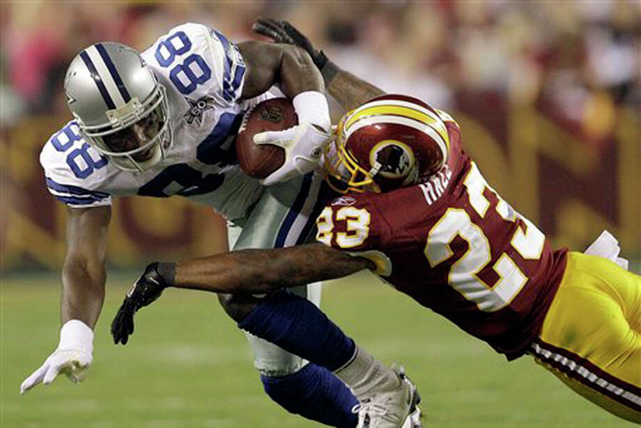Dallas Cowboys wide receiver Dez Bryant is stopped by Washington Redskins cornerback DeAngelo Hall during the first half of an NFL football game in Landover, Md., on Sunday, Sept. 12, 2010. Photo: Evan Vucci/AP / AP