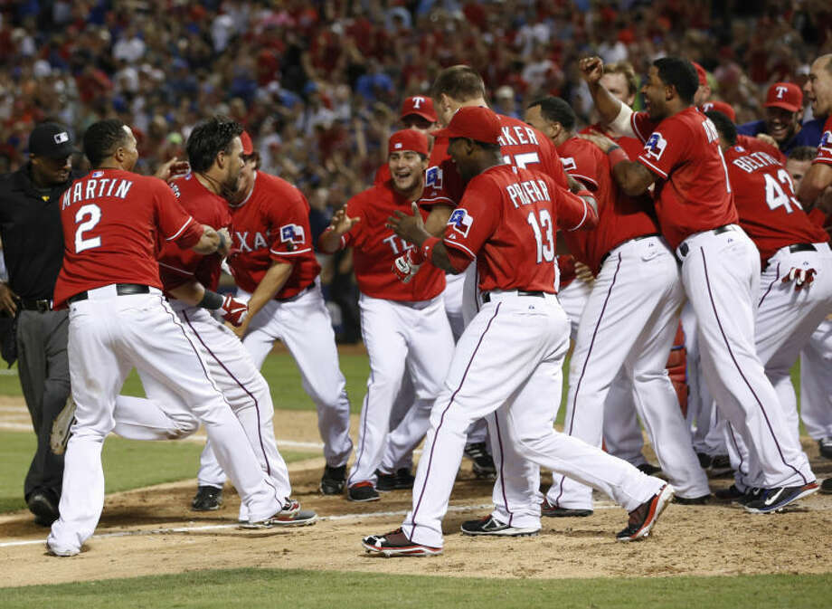 Texas Rangers' Geovany Soto, second from left, is met by teammates after hitting a walk-off home run against the Los Angeles Angels on July 29 in Arlington. The Rangers won 4-3. (AP Photo/Jim Cowsert) Photo: Jim Cowsert