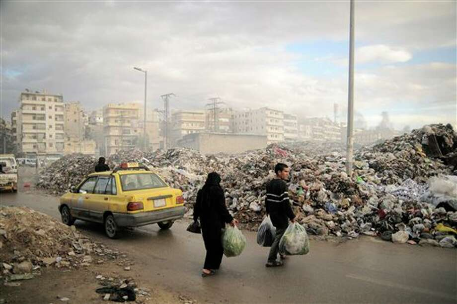 In this Saturday, Nov. 10, 2012 photo, Syrians carry their rubbish to a mountain of garbage in a roundabout in Aleppo, Syria. Due the heavy fighting and shelling, the garbage collection system collapsed weeks ago. (AP Photo/Mónica G. Prieto) Photo: Mónica G. Prieto / AP
