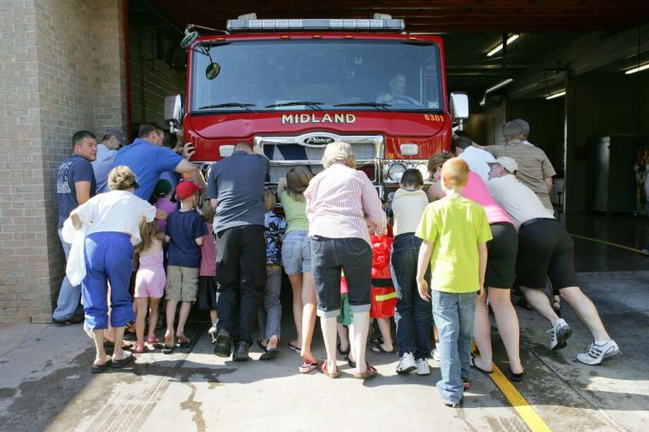 "(File Photo) ""Housing"" Ceremony participants push Midland Fire Departments newest fire engine into the station, to signify it's ready for use, Saturday at Station 8. Cindeka Nealy/Reporter-Telegram Photo: Cindeka Nealy"