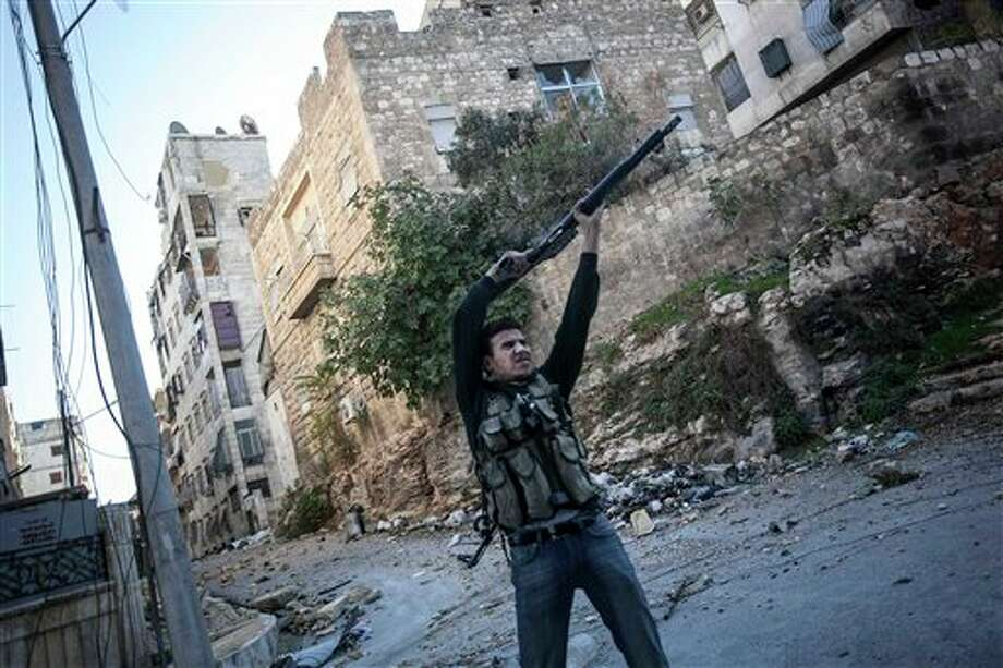 In this Wednesday, Nov. 14, 2012 photo, a Syrian rebel fighter aims at Syrian government forces during skirmishes in Aleppo, Syria. (AP Photo/Narciso Contreras) Photo: Narciso Contreras / AP
