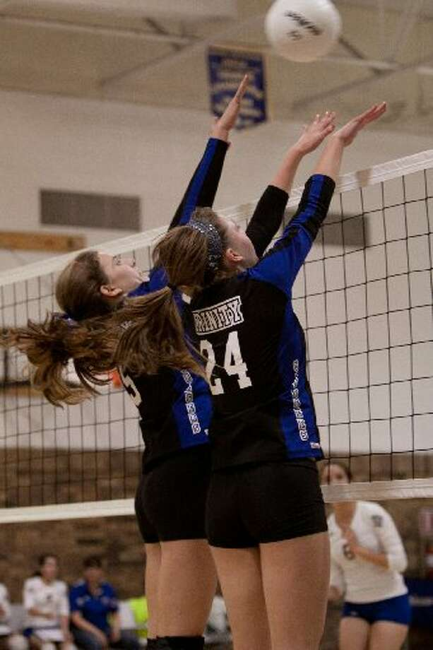 Trinity volleyball players Olivia Fryt (24) and Maddie Farish go up for a block during Saturday's TCAF district match at El Paso Immanuel. The Lady Chargers won the match in three games.Photo by Claire Heck