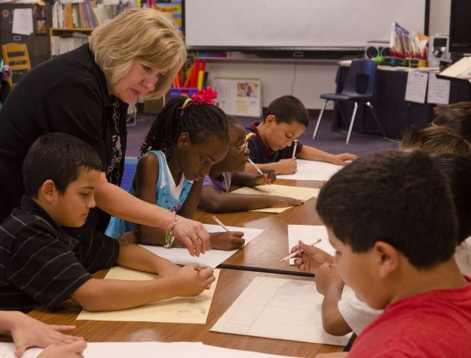 Bevra Carruth, music and arts teacher at Travis Elementary, looks over some of her students posters as they work on their fire prevention poster to be entered at the Midland Fire Department for Fire Prevention Week, October 10-14. Photo by Tim Fischer/Midland Reporter-Telegram Photo: Tim Fischer