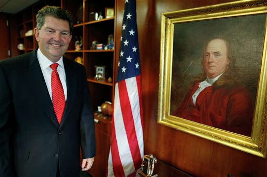 Postmaster General Patrick R. Donahoe poses with next to a portrait of Benjamin Franklin, the first postmaster general, after an interview with the Associated Press at his office at U.S. Postal Service Headquarters in Washington, Thursday, Aug. 1, 2013. Donahoe has a wish list for raising cash for his financially ailing agency. High on it is delivery of beer, wine and spirits. In an interview with The Associated Press, Donahoe also endorsed ending most door-to-door and Saturday mail deliveries as cost-saving measures. (AP Photo/Charles Dharapak) Photo: Charles Dharapak / AP