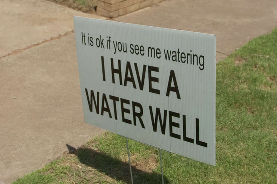 Some residents have placed signs in their yard to inform others they use a water well to help water htre yard. Photo by Tim Fischer/Midland Reporter-Telegram Photo: Tim Fischer
