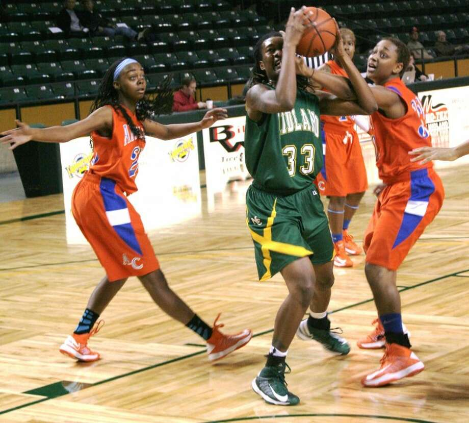 Midland College's Achiri Ade is fouled by Angelina's DeAnna Waters while going to the basket during their game on Friday at Chaparral Center. Midland College won 96-76 to advance to Saturday's consolation championship of the Midland College National Invitational Tournament.