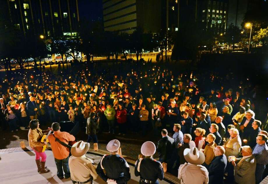 Midlanders gather in Centennial Plaza Saturday for a candlelight vigil held in honor of four veterans who were killed when a freight train hit a parade float Thursday. James Durbin/Reporter-Telegram Photo: JAMES DURBIN