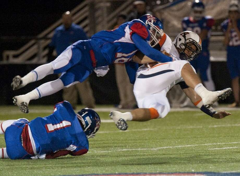 Midland Christian's Chase Standard hangs on to Brook Hill's Will Weathers as they both trip over Blaine Perkins Friday night at Mustang Field. Weathers injured his ankle on the play and was out the rest of the game. Tim Fischer\Reporter-Telegram Photo: Tim Fischer