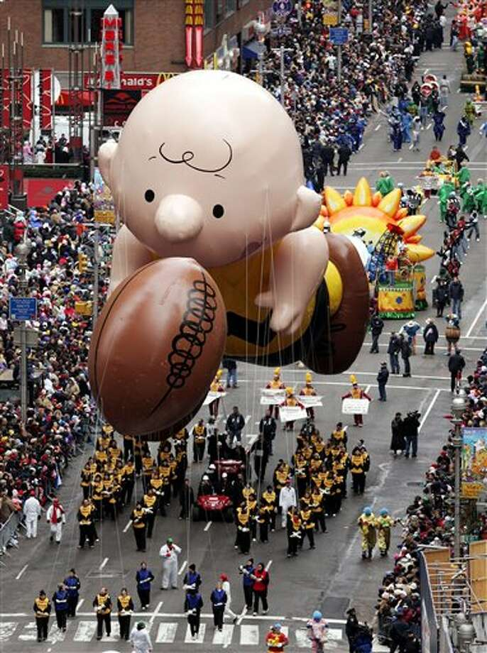 FILE - This Nov. 24, 2005 file photo shows a balloon of Peanuts character Charlie Brown chasing a football down Broadway during the Macy's Thanksgiving Day parade in New York. The parade has to be a crowd-pleaser for a multigenerational crowd. More than 3 million people typically attend the event that also unfolds in front of a TV audience of 50 million. This year's parade will feature balloons include Papa Smurf and the Elf on a Shelf, while Buzz Lightyear, Sailor Mickey Mouse and the Pillsbury Doughboy keep their place in the lineup. A new version of Hello Kitty is also to be included. (AP Photo/Jeff Christensen, file) Photo: JEFF CHRISTENSEN / AP