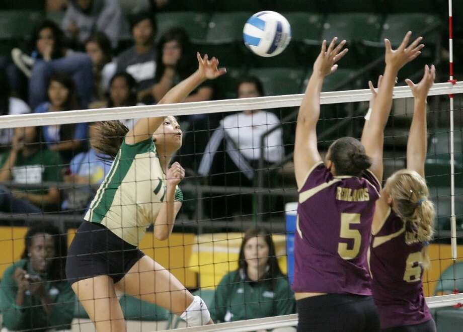 Midland College's Brittany Serrano attempts to spike the ball past Redlands' Latisha Brittenham, left, and Carina Emsermann during the Midland College Invitational at Chaparral Center. Photo: Cindeka Nealy