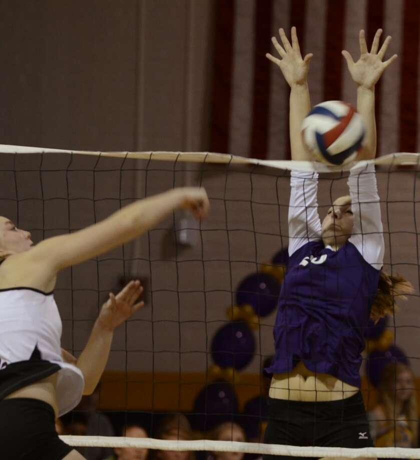 Midland High's Jenna Gilleon attempts to block Lee High's Landry Johnson Friday evening at MHS. Photo by Tim Fischer/Midland Reporter-Telegram Photo: Tim Fischer