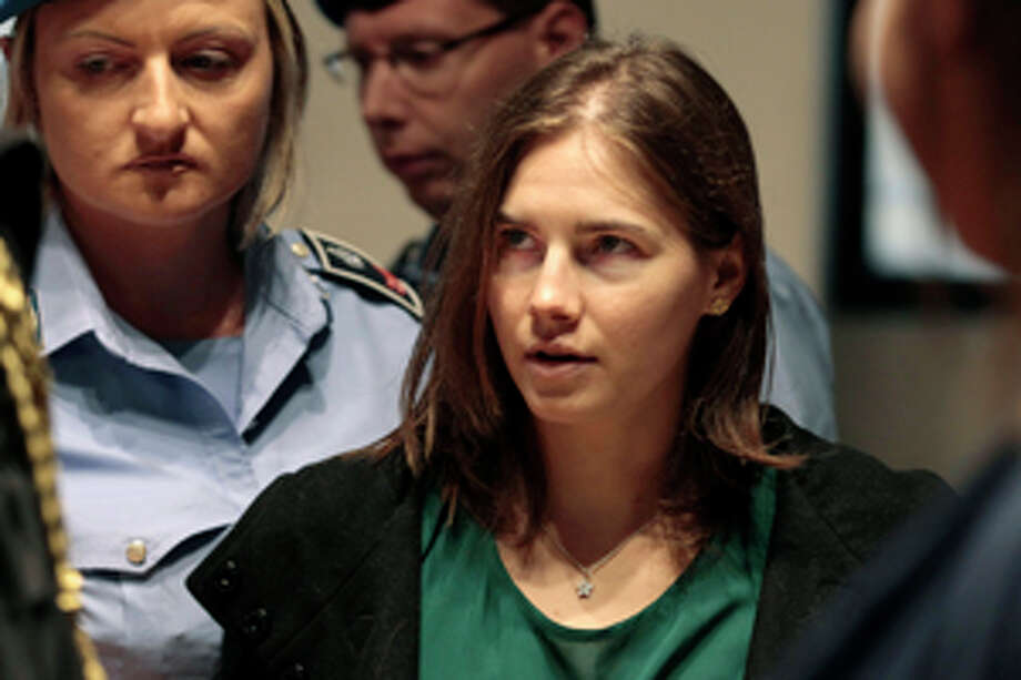 Amanda Knox is escorted as she arrives for an appeal hearing at the Perugia court, central Italy, Monday, Oct. 3, 2011. The 24-year-old Knox looked tense as she entered a packed courthouse. She is expected to address the court in a final plea of her innocence. A verdict is expected later Monday. (AP Photo/Pier Paolo Cito) Photo: Pier Paolo Cito / AP