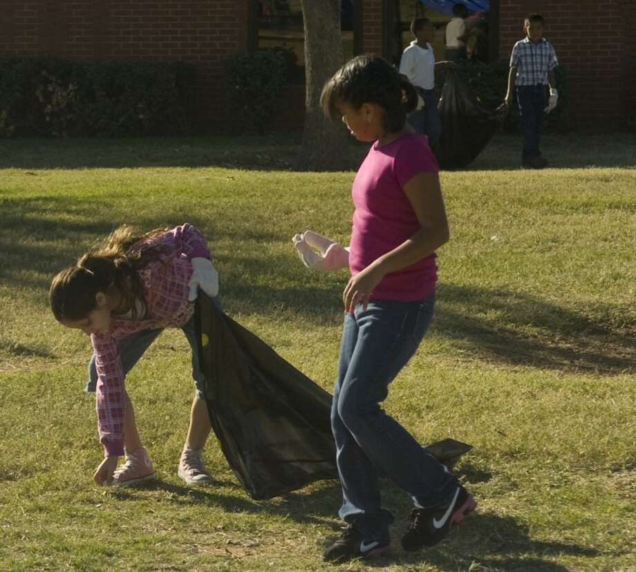Naomi Galan, left, and Gaby Gonzales, along with other Travis Elementary School students picked up trash outside the school a year ago as part of Keep Midland Beautiful's Make a Difference Day Fall Cleanup.   Photo: MRT File Photo