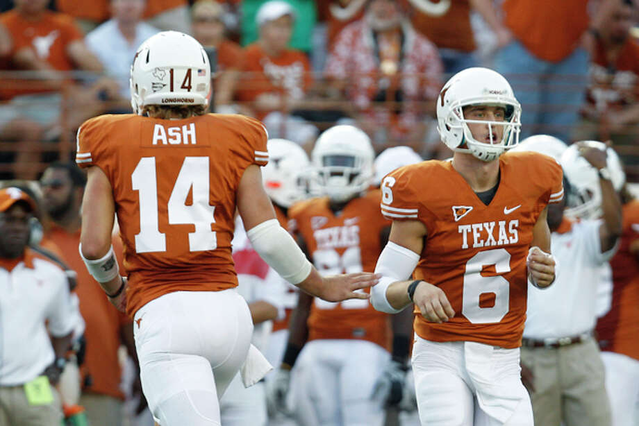 FILE - This Sept. 10, 2011 file photo shows Texas quarterbacks David Ash (14) and Case McCoy (6) passing during the first quarter of an NCAA college football game against BYU, in Austin, Texas. The quickest way to win the hearts of Longhorns fans is to beat the Sooners. Case McCoy and David Ash will get their first chance to do that on Saturday when No. 11 Texas (4-0, 1-0 Big 12) and No. 3 Oklahoma (4-0, 1-0) clash. (AP Photo/Eric Gay, File) Photo: Eric Gay / AP2011