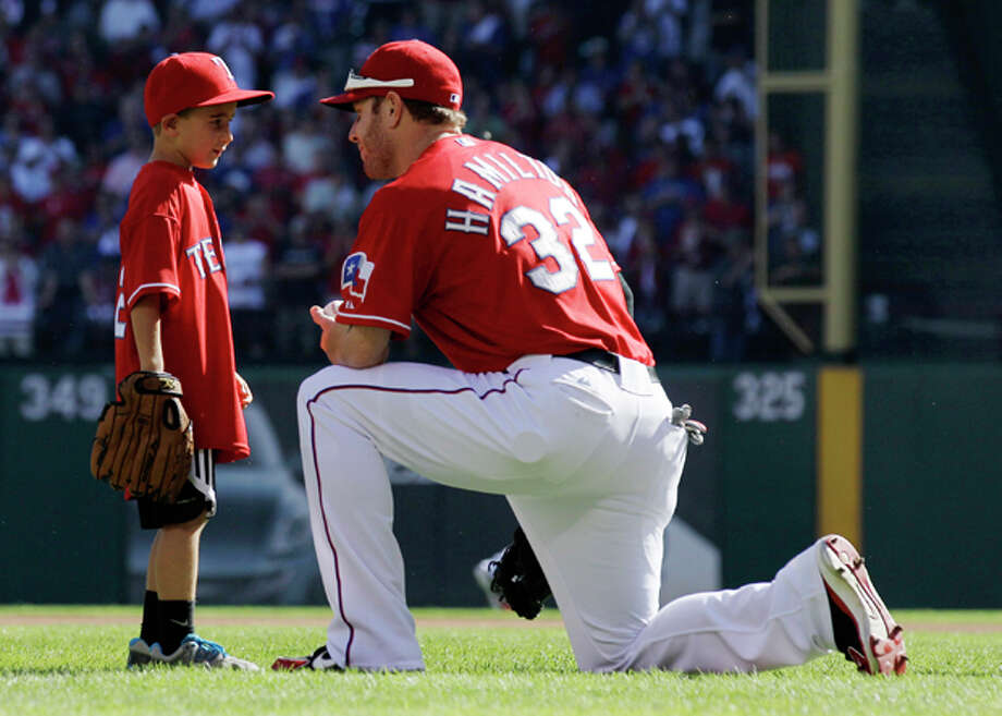 After throwing out a ceremonial first pitch, Cooper Stone, 6, talks with Texas Rangers left fielder Josh Hamilton (32) before Game 1 of baseball's American League division series playoffs against the Tampa Bay Rays Friday, Sept. 30, 2011, in Arlington, Texas. Hamilton threw the ball Shannon Stone was reaching for when he fell to his death behind the outfield wall in July. (AP Photo/Tony Gutierrez) Photo: Tony Gutierrez / AP