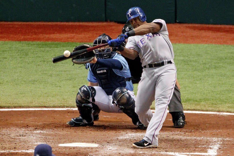 Texas Rangers' Adrian Beltre, right, hits a solo home run in front of Tampa Bay Rays catcher Kelly Shoppach and umpire Greg Gibson during the seventh inning of Game 4 of baseball's American League division series, Tuesday Oct. 4, 2011, in St. Petersburg, Fla. (AP Photo/Mike Carlson) Photo: Mike Carlson / FR155492 AP