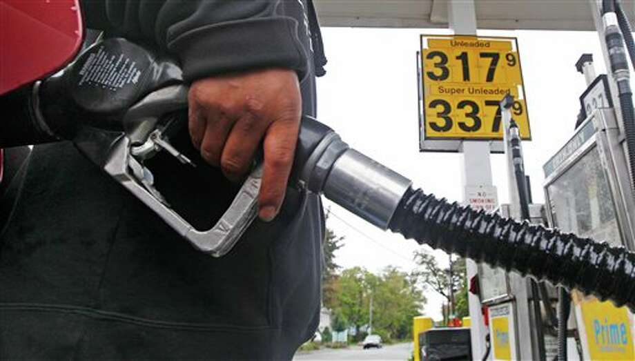 A gas station attendant fills up an automobile's tank with the gallon price of $3.17 in Wakefield, Mass., Tuesday, Oct. 4, 2011. Oil tumbled to below $76 a barrel Tuesday as fears intensified that Greece may not be able to crawl out from beneath a mountain of debt without defaulting.(AP Photo/Charles Krupa) Photo: Charles Krupa / AP2011