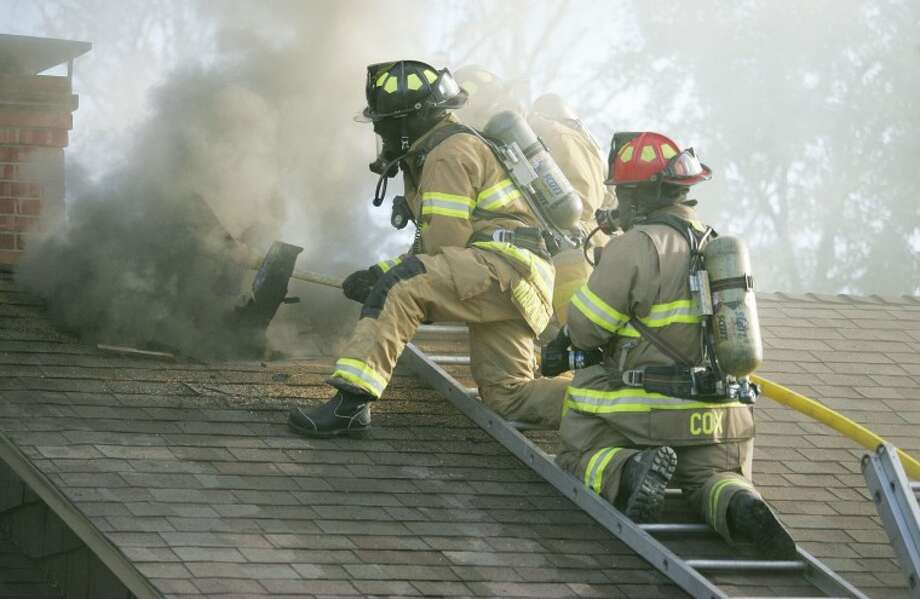Midland firefighters cut a vent hole into the roof as they battle a fire Monday at 1703 Harvard Ave. Photo: Cindeka Nealy/Reporter-Telegram