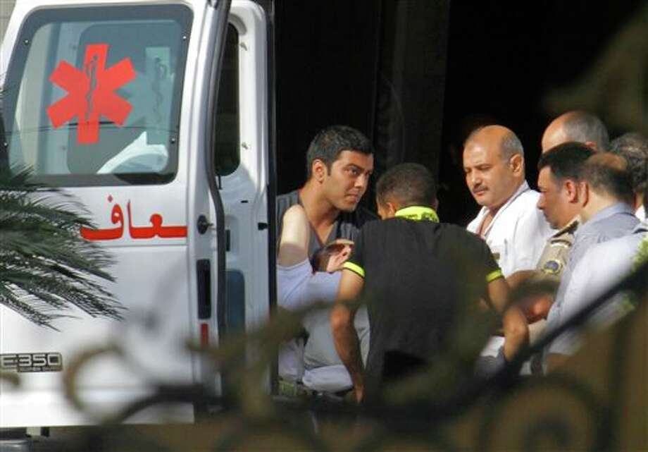Medics escort former Egyptian President Hosni Mubarak, 85, into an ambulance after after he was flown by a helicopter ambulance to the Maadi Military Hospital from Tora prison in, Cairo, Thursday, Aug. 22, 2013. Mubarak has been released from jail and taken to military hospital in Cairo. (AP Photo/Amr Nabil) Photo: Amr Nabil / AP