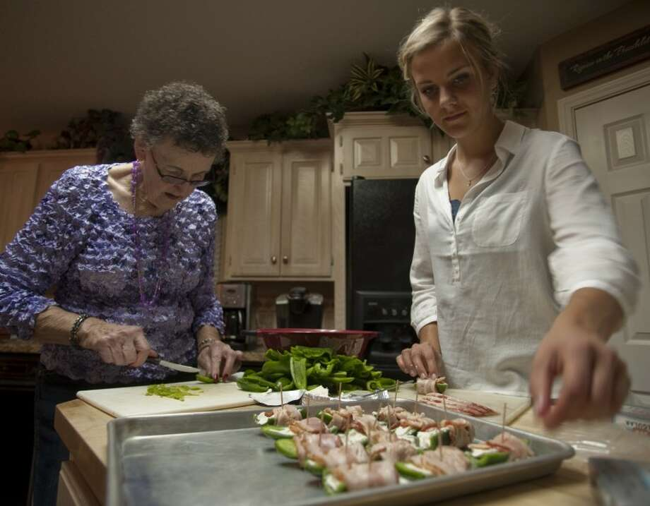 Norwegian exchange student Sara Haaland, staying with the Hancock family, helps Anette Staples make bacon wrapped jalapenos Tuesday evenig as Sara helps prepare for a big family Thanksgiving. Tim Fischer\Reporter-Telegram Photo: Tim Fischer