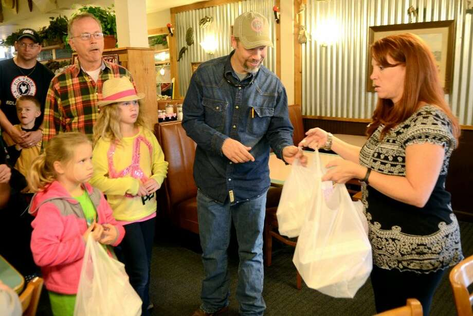 Delaney McCaghren and daughters Ali, age 7, and Libby Kate, age 9, pick up Thanksgiving meals from Way Out West Steakhouse in Midland before delivering them to the elderly Thursday. The event was put on by members of the Indian Guides and Princesses and according to event organizers 196 meals were delivered throughout Midland that morning. James Durbin/Reporter-Telegram Photo: JAMES DURBIN