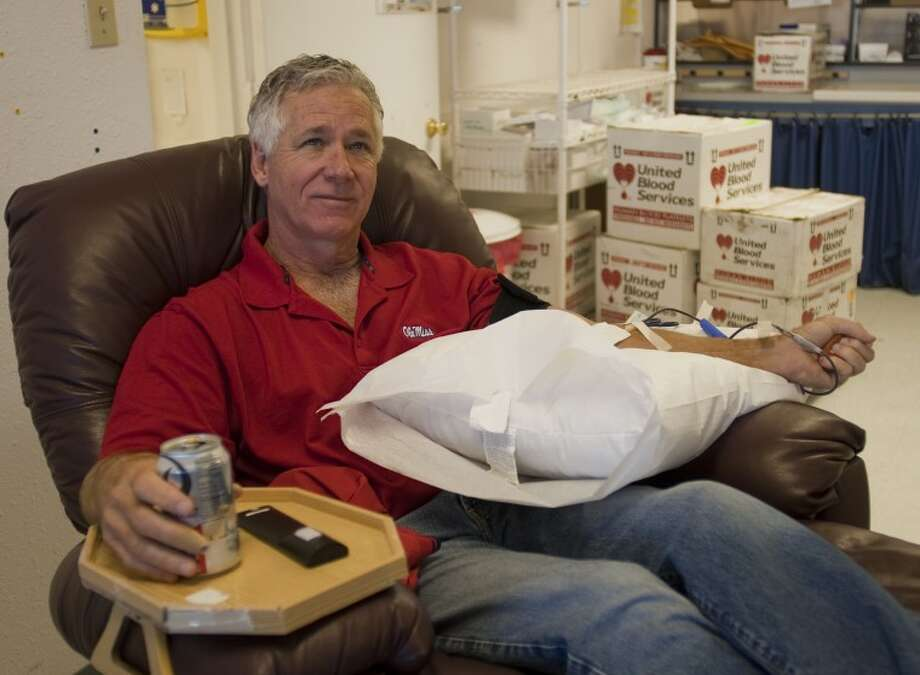 Jim Harrison, a regular donar, sits back and watches TV as he donates blood Friday at United Blood Services. Tim Fischer\Reporter-Telegram Photo: Tim Fischer