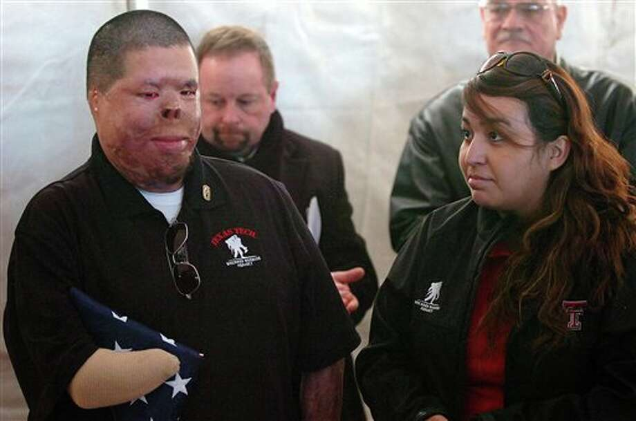 In this Monday, Feb. 7, 2011 photo, Anthony Villarreal and Jessica Villarreal listen during a ceremony Feb. 7, 2011 in Lubbock, Texas dedicating a home being built for them by Operation Finally Home. A 2008 IED attack in Afghanistan left him with third-degree burns over nearly 70 percent of his body. His face is disfigured, his right hand gone, his left hand missing fingers. In 2001, Anthony Villarreal was a 15-year-old high school sophomore, inspired by 9/11 to join the military. At 25, he is a disabled but determined veteran trying to fashion a new life, but sometimes missing his old one. (AP Photo/Lubbock Avalanche-Journal, John Bowersmith) Photo: John Bowersmith / Lubbock Avalanche-Journal