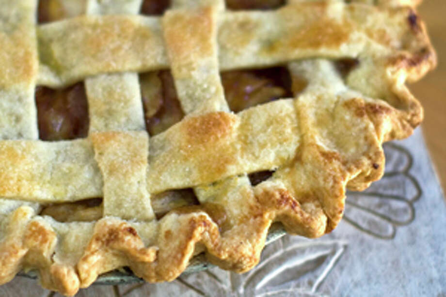 This Sept. 19, 2011 photo shows classic lattice apple pie in Concord, N.H. The key to this recipe is to slightly cook the apples before spooning them into the unbaked crust. This prevents them from deflating during cooking. (AP Photo/Matthew Mead) Photo: Matthew Mead / FR170582 AP