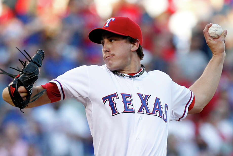 Texas Rangers starting pitcher Derek Holland (45) delivers the ball to the Tampa Bay Rays during the first inning of Game 2 of baseball's American League division series playoffs, Saturday, Oct. 1, 2011, in Arlington, Texas. Photo: (AP Photo/LM Otero) / AP