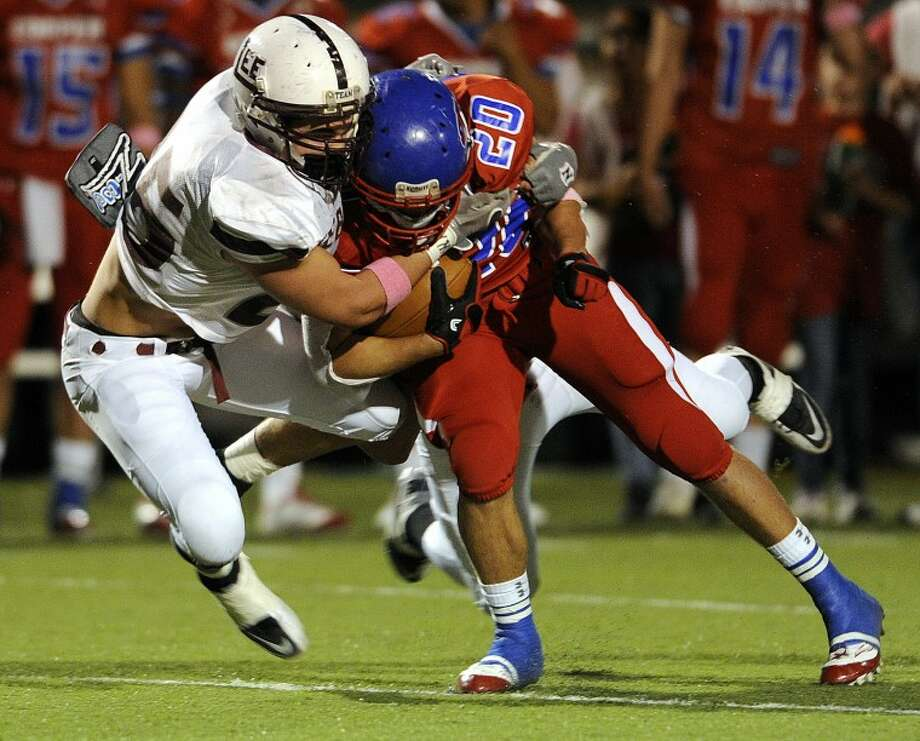 Midland Lee linebacker Luke Stice (25) tackles Cooper running back Matt Watson (25) during the first quarter of Lee's game on Friday, Oct. 7, 2011, at Shotwell Stadium in Abilene. (Photo by Tommy Metthe/Abilene Reporter-News) Photo: Tommy Metthe