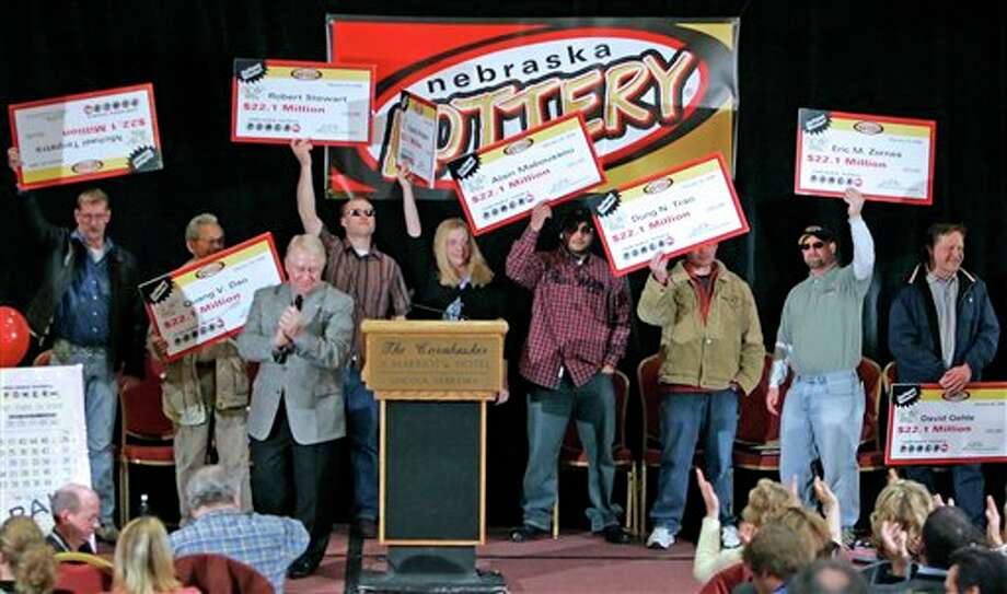 FILE- In this Feb. 22, 2006, file photo, the eight winners of the $365 million Nebraska Powerball lottery hold up their ceremonial checks at a news conference in Lincoln, Neb. As the drawing for a $500 million Powerball jackpot approaches, Wednesday, Nov. 28, 2012, past winners of mega-lottery drawings and financial planners have some advice: stick to a budget, invest wisely, learn to say no and be prepared to lose friends while riding an emotional roller-coaster. (AP Photo/Nati Harnik, File) Photo: Nati Harnik / A2006