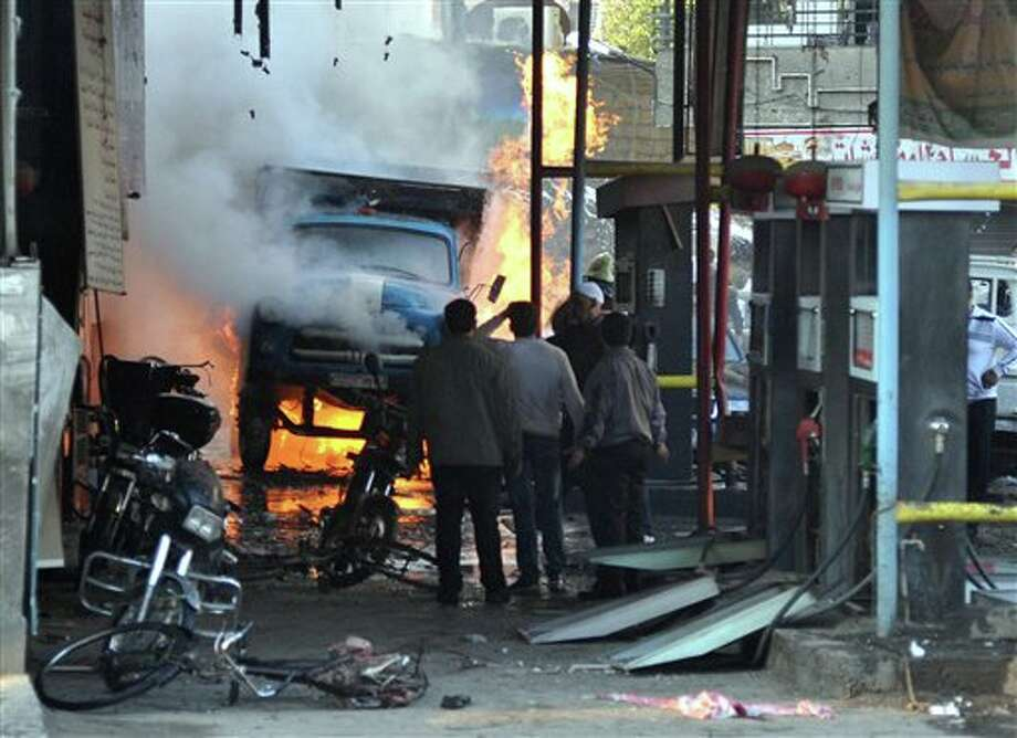In this photo released by the Syrian official news agency SANA, Syrian citizens stand near a burning truck that was destroyed by two cars bombs, at Jaramana neighborhood, in the suburb of Damascus, Syria, Wednesday, Nov. 28, 2012. (AP Photo/SANA) Photo: HOPD / SANA