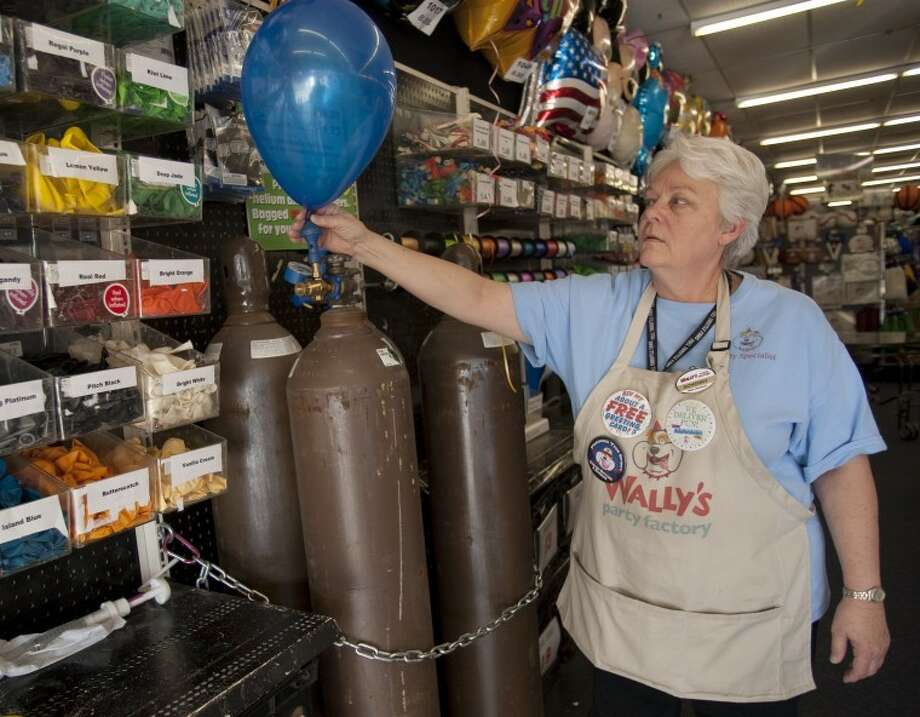 Scherry Gatewood, assistant manager at Wally's Party Factory, fills a balloon with helium Tuesday afternoon. Tim Fischer\Reporter-Telegram Photo: Tim Fischer