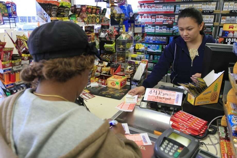 In this photo taken Tuesday, Nov. 27, 2012, Roselyn Jones purchases a few Powerball tickets from station attendant Claudia Molina at the Conoco Sunrise Market off of Brainerd Road in Chattanooga, Tenn. The historic Powerball jackpot boosted to $500 million on Tuesday was all part of a plan lottery officials put in place early this year to build jackpots faster, drive sales and generate more money for states that run the game. (AP Photo/Chattanooga Times Free Press, Dan Henry) THE DAILY CITIZEN OUT; NOOGA.COM OUT; CLEVELAND DAILY BANNER OUT; LOCAL INTERNET OUT Photo: Dan Henry
