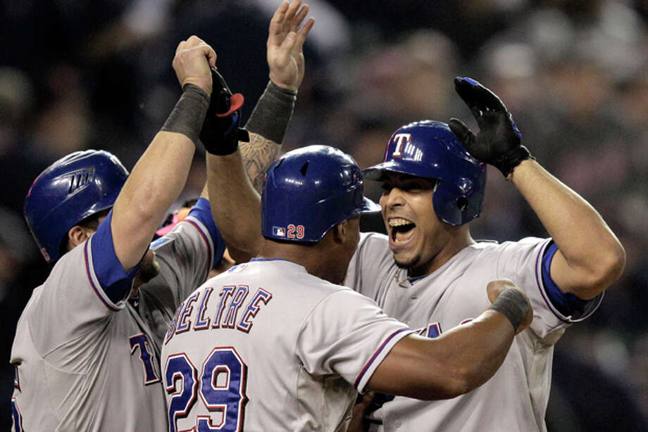 Texas Rangers' Adrian Beltre and Mike Napoli celebrate with teammate Nelson Cruz after his 3-run home run in the 11th inning in Game 4 of baseball's American League championship series against the Detroit Tigers, Wednesday, Oct. 12, 2011, in Detroit. (AP Photo/Charlie Riedel) Photo: Charlie Riedel / AP