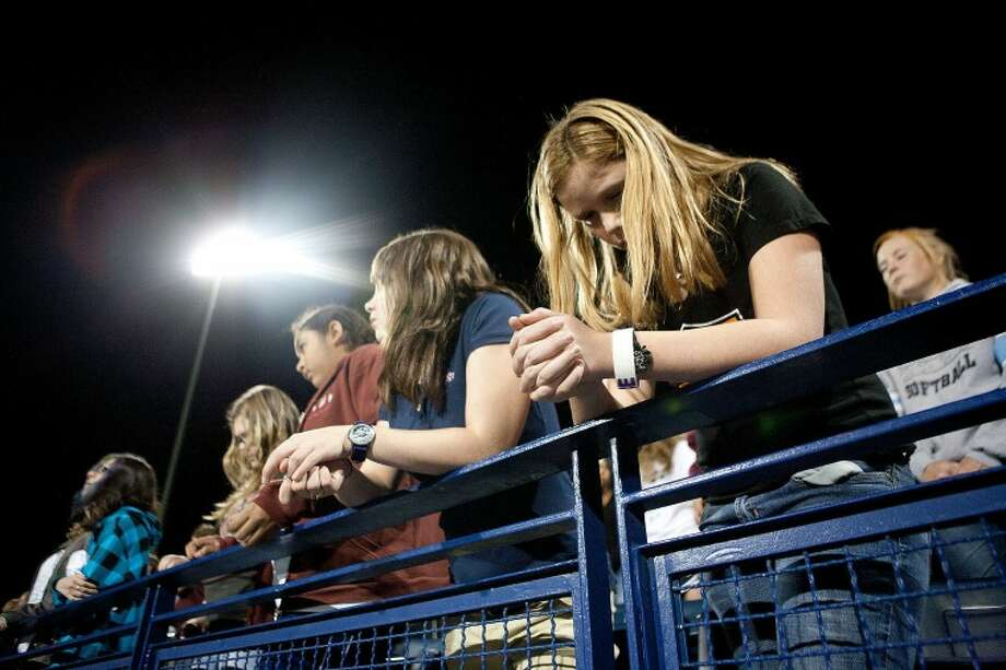 Gracy Walls, 12, bows her head to pray during the annual Fields of Faith at Grande Communications Stadium. Photo: MRT File Photo