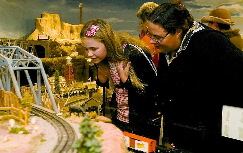 Laura Leigh Clinton and her sister Allison look at the train exhibit as part of Christmas at the Mansion during an open house Monday evening. Photo: Tim Fischer